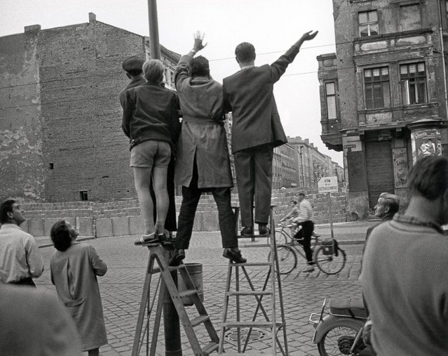 West Berlin inhabitants wave at the newly erected Berlin Wall in 1961. (Photo by Imagno/Getty Images)