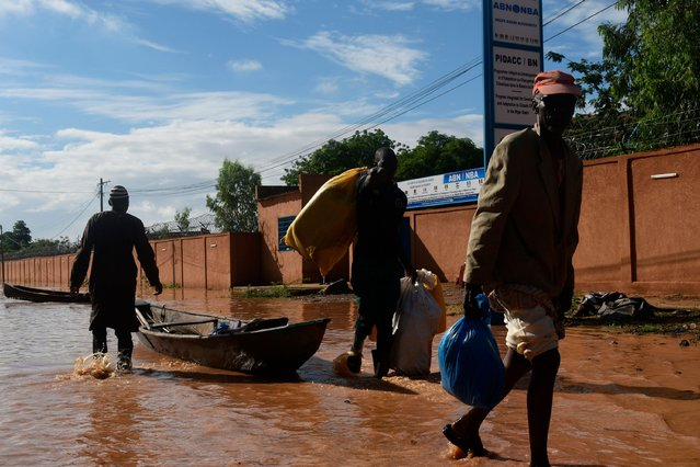 Residents carry their belongings after they left their flooded houses in Niamey on August 25, 2020, after heavy rains in Niger. (Photo by Boureima Hama/AFP Photo)