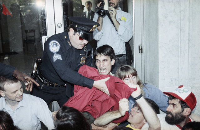 U.S. Capital Police take a banner away from a protester on Monday, October 16, 1989 as demonstrators attempted to block a Capitol Hill congressional office building in protest of U.S. military aid to El Salvador. Forty one of the demonstrators were arrested at the protest. (Photo by Rick Bowmer/AP Photo)