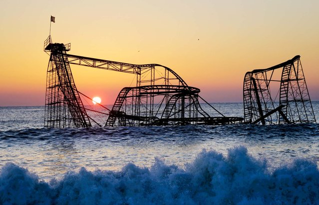 The sun rises in behind the Jet Star Roller Coaster in Seaside Heights, New Jersey, February 25, 2013. The coaster has been sitting in the ocean after part of the Funtown Pier collapsed during Superstorm Sandy. The owners are working with insurers to devise a plan to dismantle the ride and get it out of the ocean. (Photo by Mel Evans/Associated Press)