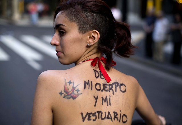 "A woman with a message painted on her back that reads in Spainsh ""My body, my wardrobe"" participates in a demonstration marking International Women's Day in Buenos Aires. (Photo by Victor R. Caivano/Associated Press)"