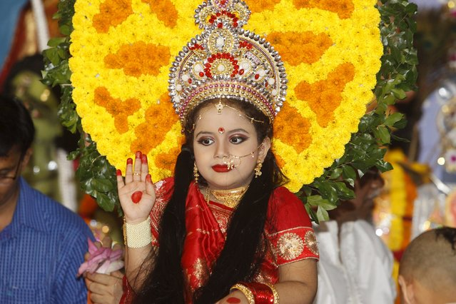 "A Hindu virgin girl dressed as ""Kumari"" sits a on dais to be worshipped as a symbol of purity and representative of Devi Durga during the celebration of the Kumari Puja, in Dhaka's Ramakrishna Mission, Bangladesh October 21, 2015. Kumari Puja is a part of biggest Hindu festival Durga Puja. Hindus believe that the goddess Durga symbolises power and the triumph of good over evil. (Photo by Ashikur Rahman/Reuters)"