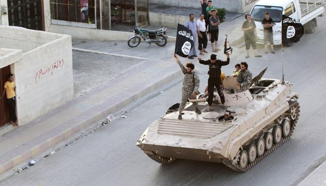 Militant Islamist fighters take part in a military parade along the streets of northern Raqqa province, in this June 30, 2014 file photo. (Photo by Reuters/Stringer)