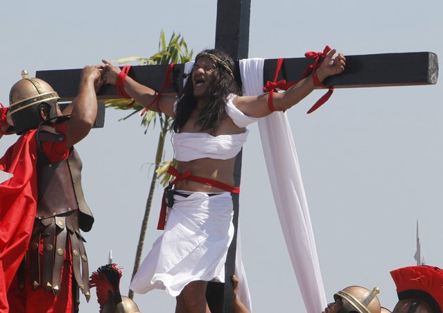 Ruben Enaje, 52, who is portraying Jesus Christ for the 27th time, screams while a man playing a Roman soldier pulls out a nail from his palm after he was nailed on a wooden cross during a Good Friday crucifixion re-enactment in San Pedro Cutud town, Pampanga province, north of Manila March 29, 2013. About two dozen Filipinos were nailed to crosses on Good Friday in an extreme display of devotion that the Catholic church looks down upon as a form of folk religion but appears powerless to stop. Holy Week is celebrated in many Christian traditions during the week before Easter. (Photo by Romeo Ranoco/Reuters)