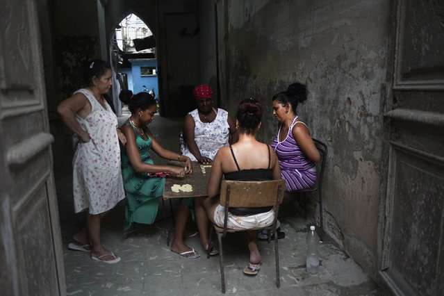 In this September 16, 2015, file photo, women play dominoes in a building courtyard in Old Havana, Cuba. The sprouting of high-end clubs and bars around Havana is unsettling to many in Cuba who grew up believing in equality as a tenet of the revolution, and now see foreigners and wealthy Cubans spending many times in one night the roughly $30 monthly salary of the average Cuban state worker. (Photo by Ramon Espinosa/AP Photo)