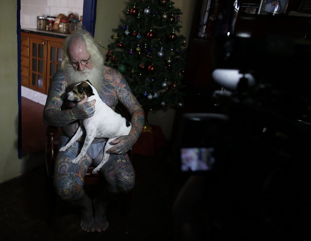 Vitor Martins holds his dog during an interview with Reuters inside his house, before a performance with children in Sao Caetano do Sul's town square, near Sao Paulo, December 7, 2014. (Photo by Nacho Doce/Reuters)
