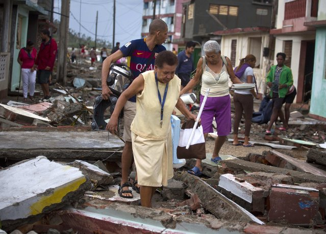 People carry some of their belongings through the rubble of a street after the passing of Hurricane Matthew in Baracoa, Cuba, Wednesday, October 5, 2016. (Photo by Ramon Espinosa/AP Photo)