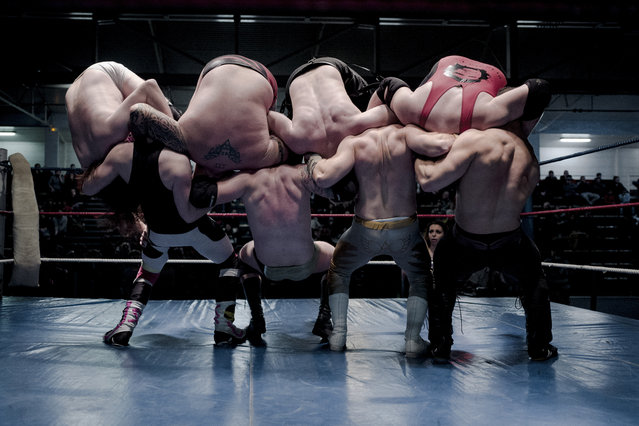 In this photo dated Saturday, February 24, 2018 (L to R) wrestlers Nelson Fernandes, Alex Legrand, Ace Angel, and Zach, bottom, headlock wrestlers Lord Steven Crowley, Darkmundo, Maeven, and PV Red, fight during a wrestling charity gala in Ivry-sur-Seine, south of Paris, France. With revolutionary slogans and a message of support for the unemployed, this was no ordinary wrestling match. (Photo by Kamil Zihnioglu/AP Photo)