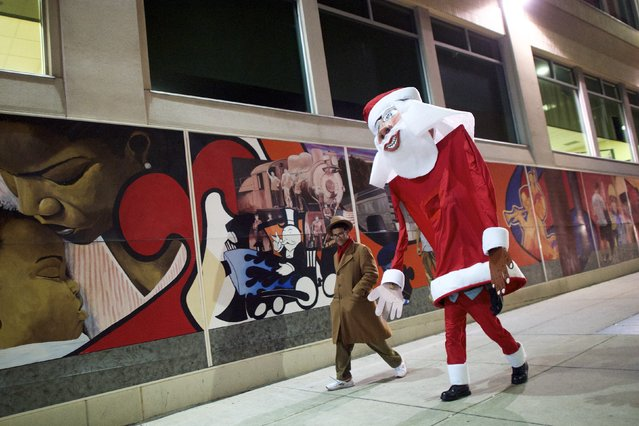 A giant Santa Claus, created and worn by local artist Ed Terrell, 66, walks home with his son and assistant, Rupanuga, 18, following a ceremony to decorate a scraggly Christmas tree with a single red Bulb in Reading, Pennsylvania, December 7, 2014. A ceremony to decorate the scraggly Christmas tree in Reading, Pennsylvania with a single red bulb, much like Charlie Brown's tree in the animated holiday classic, was postponed to Sunday from Saturday because of rain and cold temperatures, officials said. (Photo by Mark Makela/Reuters)