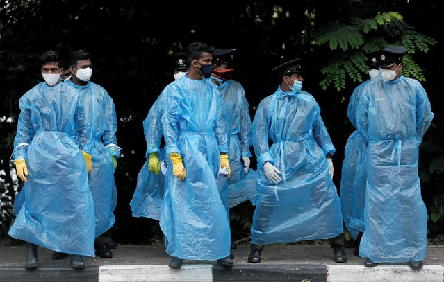 Police officers wearing protective gear stand in formation near the parliament during a protest against a proposed constitution amendment, amid concerns about the spread of the coronavirus disease (COVID-19), in Colombo, Sri Lanka, October 21, 2020. (Photo by Dinuka Liyanawatte/Reuters)