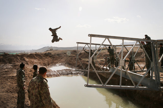 A soldier with the Afghan National Army's (ANA) National Engineer Brigade tries to make dry land after leaping from the top of a Mabey-Johnson portable pre-fabricated bridge which his unit was learning to construct with the help of U.S. Navy Seabees from Naval Mobile Construction Battalion (MCB) 28 at the ANA's combined Fielding Center on March 18, 2014 in Kabul, Afghanistan. (Photo by Scott Olson/Getty Images)