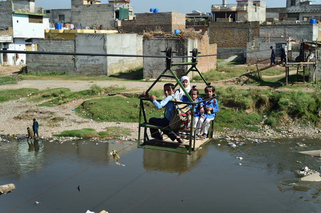 Pakistani school children sit in a trolley as they cross a polluted stream on the outskirts of Islamabad on October 22, 2015. (Photo by Farooq Naeem/AFP Photo)