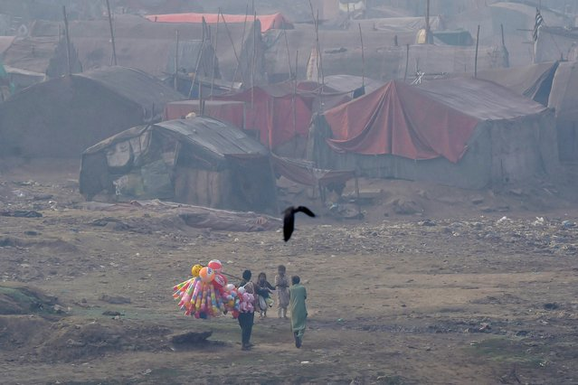 A vendor selling balloons looks for customers in a slum area amid heavy smoggy conditions in Lahore on November 13, 2020. (Photo by Arif Ali/AFP Photo)