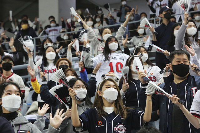 Fans wearing face masks as a precaution against the coronavirus cheer during the Game 4 of the Korean Series, the Korea Baseball Organization's championship round, between Doosan Bears and NC Dinos at Gocheok Sky Dome in Seoul, South Korea, Saturday, November 21, 2020. (Photo by Ahn Young-joon/AP Photo)