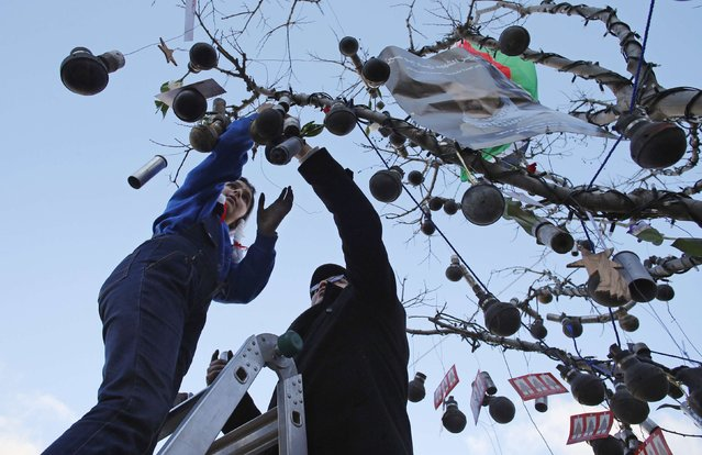 Palestinians decorate a tree with spent tear gas canisters that they said were fired by Israeli troops during clashes with Palestinian protesters, at Manger Square, ahead of Christmas, in the West Bank city of Bethlehem December 23, 2014. (Photo by Ammar Awad/Reuters)