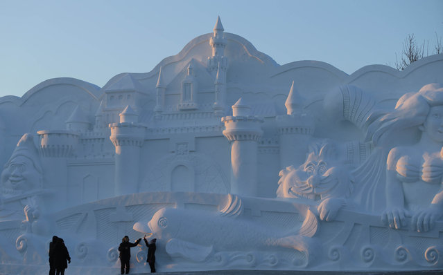Tourists pose by a snow sculpture of Disney characters in the 16th Harbin Ice and Snow World, which will officially open on January 5 on December 22, 2014 in Harbin, China. (Photo by Feature China/Barcroft Media)