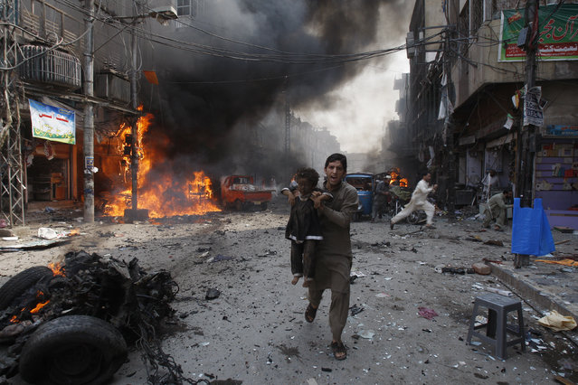 A Pakistani man carrying a child rushes away from the site of a blast shortly after a car exploded in Peshawar, Pakistan, Sunday, September 29, 2013. A car bomb exploded on a crowded street in northwestern Pakistan Sunday, killing scores of people in the third blast to hit the troubled city of Peshawar in a week, officials said. (Photo by Mohammad Sajjad/AP Photo)