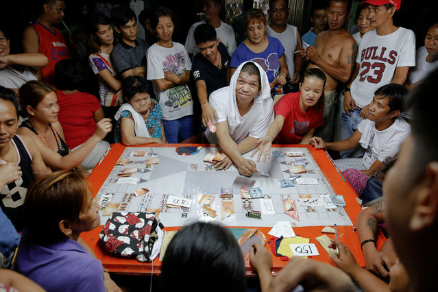Friends play cards during a wake outside the home of Florjohn P. Cruz who was killed in a police drugs buy bust operation in Manila, Philippines late October 20, 2016. (Photo by Damir Sagolj/Reuters)