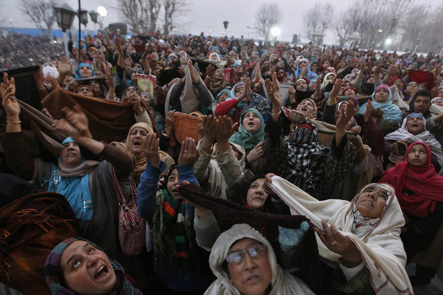 Kashmiri Muslim women raise their arms upon seeing a relic of Prophet Mohammad being displayed to devotees during the festival of Eid-e-Milad, at Hazratbal shrine on a cold winter morning in Srinagar January 4, 2015. (Photo by Danish Ismail/Reuters)