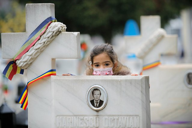 A child, wearing a mask for protection against the COVID-19 infection, leans on the cross of a 1989 anti-communist revolution victim after a memorial religious service for those killed in the uprising, in Bucharest, Romania, Monday, December 21, 2020. Participants and relatives of those killed marked the anniversary of the anti-communist uprising which started in Bucharest on Dec. 21, 1989, left more than one thousand people dead and ended the rule of dictator Nicolae Ceausescu. (Photo by Vadim Ghirda/AP Photo)