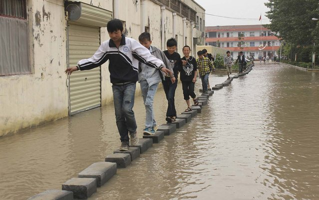 Students were forced to walk on bricks laid out along a road after the rain, at a school in Shangqiu, on May 28, 2013. The 150 metre long road has always flooded after rain in recent years. A project to build a raised road for the students' safety in rain was scheduled last year but has not yet beeen carried out. (Photo by Reuters/Stringer)