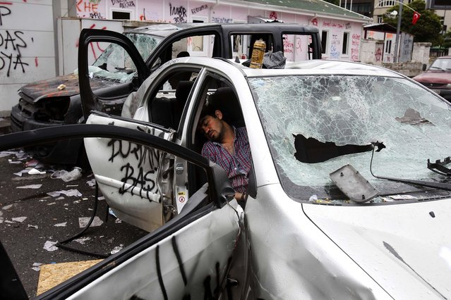 A man sleeps inside a destroyed car after clashes at Taskim Square in Istanbul, on June 2, 2013. Protests in Istanbul and several other Turkish cities appear to have subsided after days of clashes. (Photo by Thanassis Stavrakis/Associated Press)