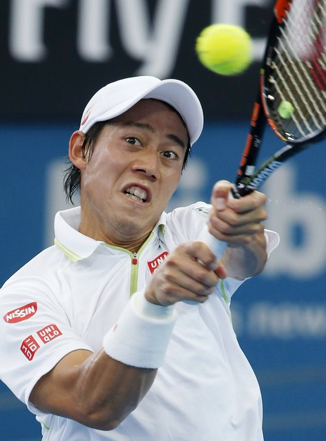 Kei Nishikori of Japan delivers a backhand return to Bernard Tomic of Australia during their men's singles quarter final at the Brisbane International tennis tournament in Brisbane, January 9, 2015. (Photo by Jason Reed/Reuters)