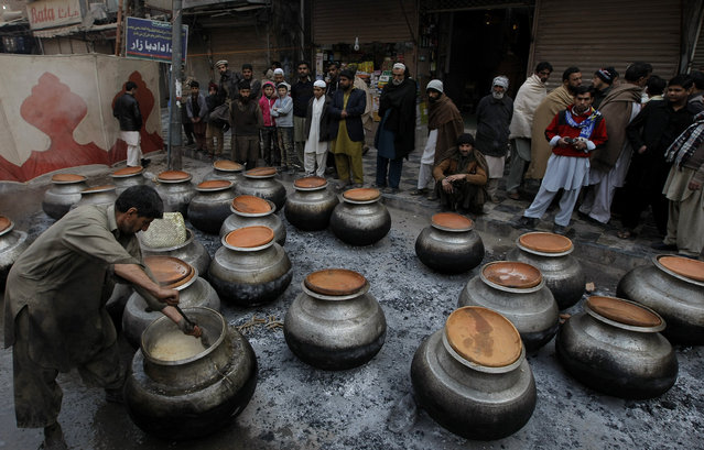 A Pakistani cook prepares food for participants of a rally marking the birthday of Islam's Prophet Muhammad in Peshawar, Pakistan, Sunday, January 4, 2015. (Photo by Anjum Naveed/AP Photo)