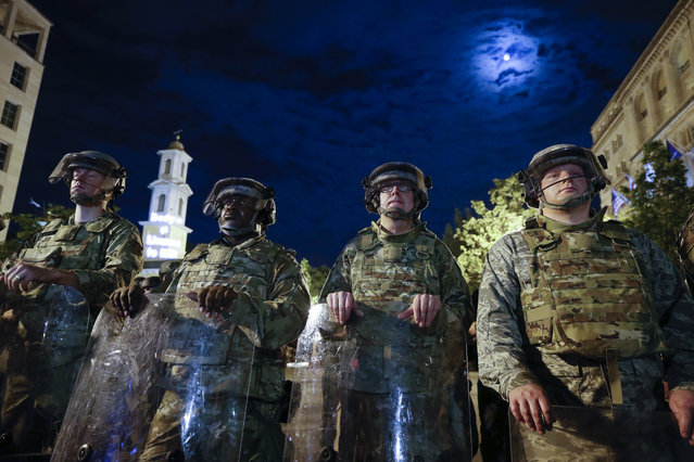 Utah National Guard soldiers stand on a police line as demonstrators gather to protest the death of George Floyd, Thursday, June 4, 2020, near the White House in Washington. Floyd died after being restrained by Minneapolis police officers. (Photo by Alex Brandon/AP Photo)