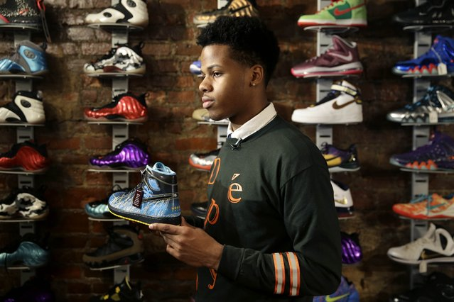 In this January 12, 2015 photo, Chase Reed holds up a sneaker while talking to a reporter at Sneaker Pawn in the Harlem section of New York. Basketball sneakers can re-sell for hundreds of dollars, depending on the model, the size of the production run and how easy it is to find a pair in good condition. (Photo by Seth Wenig/AP Photo)