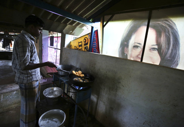 A worker prepares a traditional snack next to a banner featuring U.S. Vice President-elect Kamala Harris, lying outside a local eatery in Thulasendrapuram, the hometown of Harris' maternal grandfather, south of Chennai, Tamil Nadu state, India, Wednesday, January 19, 2021. (Photo by Aijaz Rahi/AP Photo)