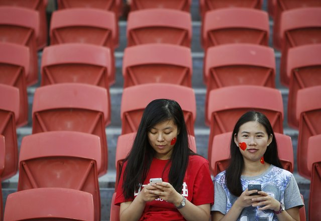 China fans use their mobile phones as they await the start of the Asian Cup Group B soccer match between China and Saudi Arabia at the Brisbane Stadium in Brisbane January 10, 2015. (Photo by Edgar Su/Reuters)