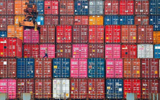A worker walks on stacks of containers at the Tanjung Priok port in Jakarta, Indonesia, January 22, 2021. (Photo by Ajeng Dinar Ulfiana/Reuters)