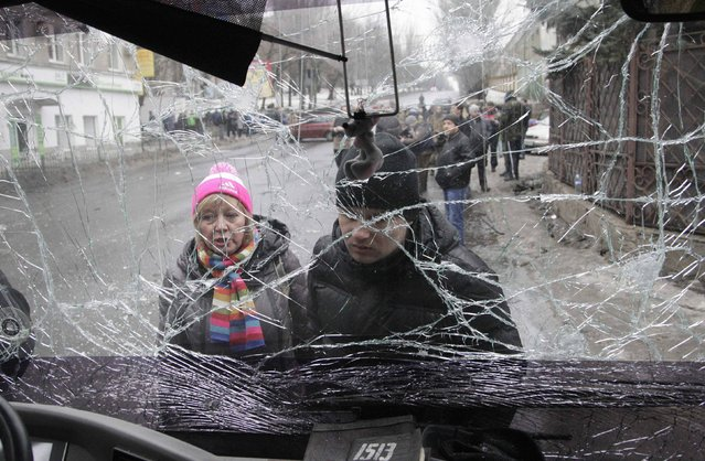 People look through the front windshield of a damaged trolleybus in Donetsk, January 22, 2015. At least seven civilians were killed on Thursday when a shell or a mortar hit a trolleybus stop in the rebel-controlled city of Donetsk in eastern Ukraine, a Reuters witness said. (Photo by Alexander Ermochenko/Reuters)