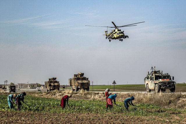 A Russian Mil Mi-17 military helicopter flies over a joint Russian-Turkish military patrol convoy in the countryside near Darbasiyah along the border with Turkey in Syria's northeastern Hasakah province on November 30, 2020. (Photo by Delil Souleiman/AFP Photo)