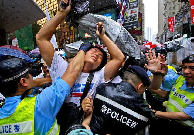 Protesters scuffle with police officers on a downtown street during an annual pro-democracy protest in Hong Kong, on July 1, 2013. Tens of thousands of the protesters demanded their widely disliked Beijing-backed leader resign and pressing for promised democratic reforms so they can choose their own top representative. The march is an annual event that underscores the growing gulf between Hong Kong and the mainland 16 years after the city ceased to be a British colony and came back under Beijing's control. (Photo by Vincent Yu/Associated Press)