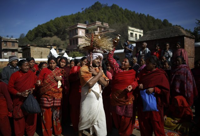 A devotee (C) sprinkles holy water towards the devotees while performing religious rituals during the Swasthani Bratakatha festival in Panauti near Kathmandu January 24, 2015. (Photo by Navesh Chitrakar/Reuters)