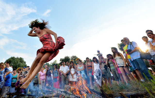 A girl jumps over a campfire while celebrating Ivan Kupala Night, a traditional Slavic holiday not far from Kiev on July 6, 2013. During the celebration, originating in pagan times, people plait wreaths, jump over fires, and swim naked. (Photo by Sergei Supinsky/AFP Photo)