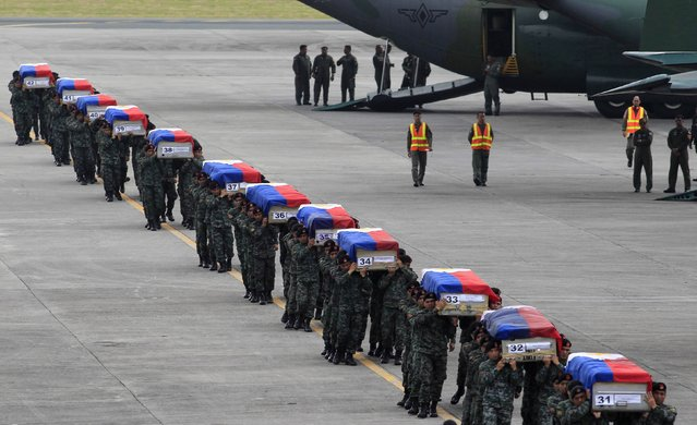 Members of the Philippine National Police's (PNP) Special Action Force (SAF) unit carry metal caskets containing the bodies of slain SAF police who were killed in Sunday's clash with Muslim rebels, upon arriving at Villamor Air Base in Pasay city, metro Manila January 29, 2015. (Photo by Romeo Ranoco/Reuters)