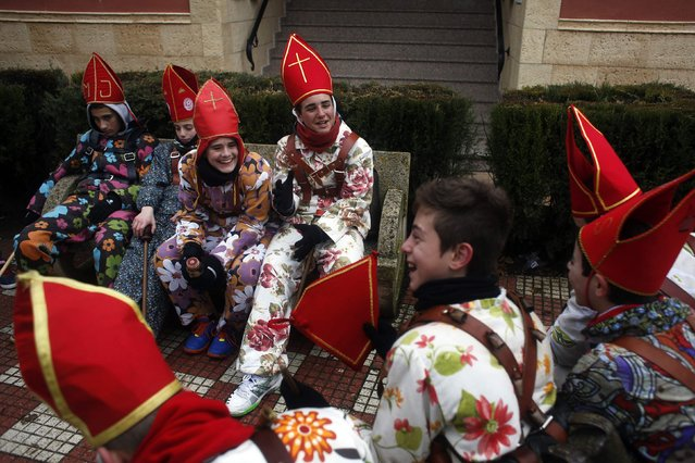"""Young believers dressed as """"diablos"""" (devils) take a break from parading around town during the """"Endiablada"""" festival in Almonacid del Marquesado, in central Spain February 3, 2015. (Photo by Susana Vera/Reuters)"""
