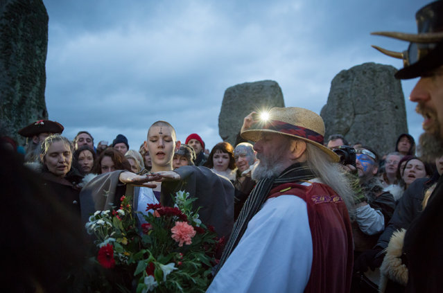 Rollo Maughfling, Archdruid of Stonehenge & Britain (C) conducts a ceremony as druids, pagans and revellers gather in the centre of Stonehenge, hoping to see the sun rise, as they take part in a winter solstice ceremony at the ancient neolithic monument of Stonehenge near Amesbury on December 22, 2015 in Wiltshire, England. (Photo by Matt Cardy/Getty Images)