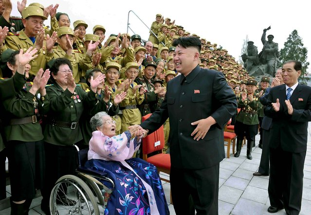 North Korean leader Kim Jong-Un laughs during a photo session with war veteran delegates who took part in the celebrations of the 60th anniversary of the signing of the truce of the Korean War, in this undated photo released by North Korea's Korean Central News Agency. (Photo by Reuters/KCNA)