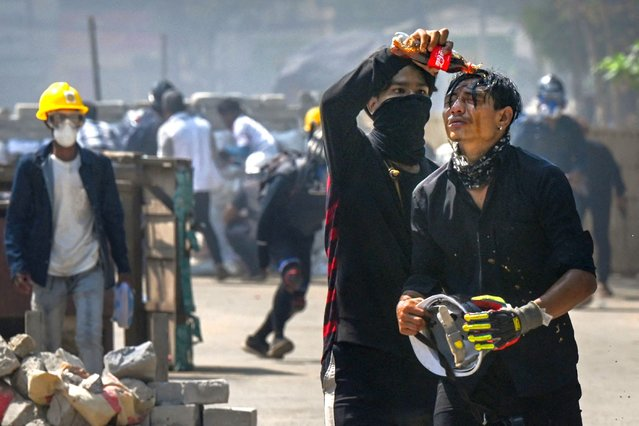 A protester pours Coca-Cola on the face of a comrade to diminish the effects of tear gas during a crackdown by security forces on a demonstration against the military coup in Yangon's Thaketa township on March 19, 2021. (Photo by AFP Photo/Stringer)