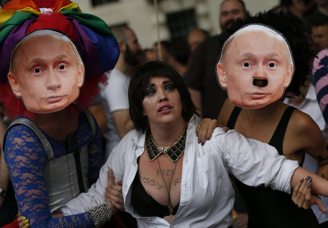 "Activists stage a theatrical play where gay people are restrained by others wearing masks depicting Russian President Vladimir Putin, during a protest against Russia's new law on gays, in central London, Saturday, August 10, 2013. Hundreds of protesters, called for the Winter 2014 Olympic Games to be taken away from Sochi, Russia, because of a new Russian law that bans ""propaganda of nontraditional sexual relations"" and imposes fines on those holding gay pride rallies. (Photo by Lefteris Pitarakis/AP Photo)"