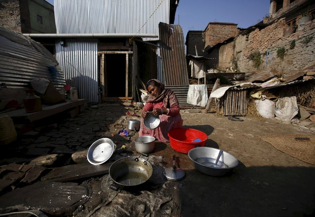 A woman washes her dishes outside the temporary shelter built near the houses damaged during an earthquake earlier this year, in Bhaktapur, Nepal December 28, 2015. (Photo by Navesh Chitrakar/Reuters)