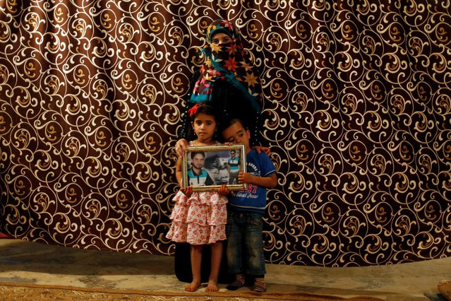 Mageda Armous, 25, the widow of a rebel fighter poses for a photograph with her children, as they hold a photograph of their late father in Zaatari camp in Jordan October 8, 2016. Armous's husband was killed during fighting againt forces loyal to Syria's President Bashar al-Assad in Daraa. (Photo by Ammar Awad/Reuters)