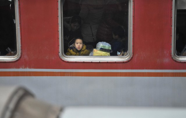 A boy looks out from the window of a train at a railway station in Hefei, Anhui province February 3, 2015. (Photo by Reuters/Stringer)