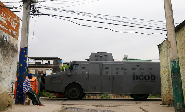 A man sits as a police armored vehicle is seen during an operation against drug dealers in City of God or City of God slum in Rio de Janeiro, Brazil, November 23, 2016. (Photo by Ricardo Moraes/Reuters)