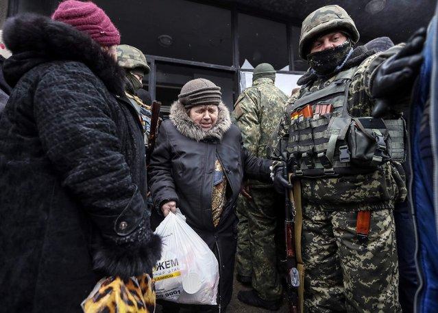 A woman carries a bag of humanitarian aid past Ukrainian servicemen in Debaltseve, eastern Ukraine, February 6, 2015. (Photo by Gleb Garanich/Reuters)