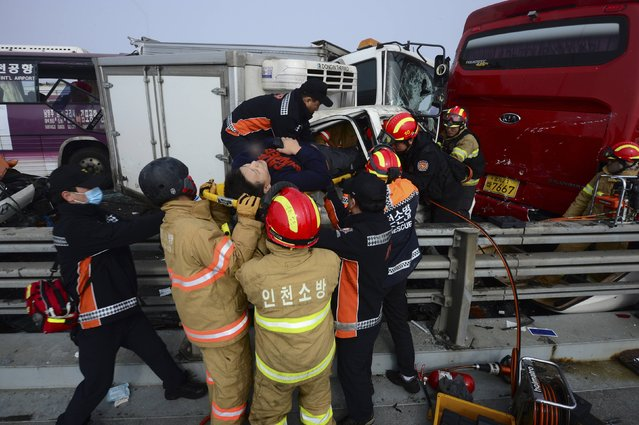 Firefighters rescue an injured man from a damaged vehicle on Yeongjong Bridge in Incheon February 11, 2015. (Photo by Park Jung-ho/Reuters/News1)